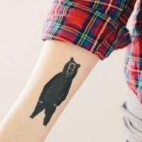 Black ink bear tattoo forearm